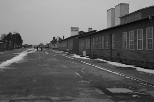 Roll call ground with the laundry facility, kitchen barrack and camp prison buildings to the right.