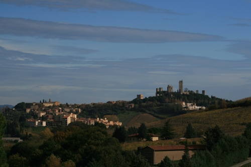 Old Town San Gimignano is to the right with all the towers.  It is surrounded by vineyards and olive trees.